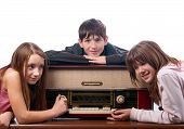 Three teenage friends listening to music on the old radio isolated on white