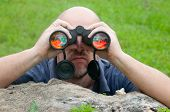 Bald man watching the nature through binoculars while leaning on old tree