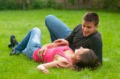 Young couple in love lying on the grass and looking at each other