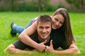 Young couple in love lying on the grass and showing thumbs up