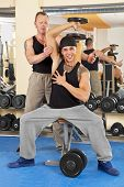 smiling young man exercising in gym with trainer