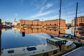 Wide Shot Of The Albert Dock In Liverpool. Boats Are Moored In The Foreground And The Liver Building poster