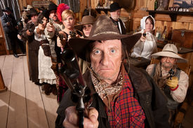 picture of gunfights  - Mean gunfighter with pistol aimed in old saloon - JPG