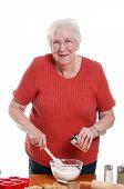 Senior Woman Adding Spices To Baking