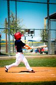 Little League Player Swinging Bat