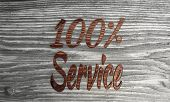 100 percent service symbol on a wooden background