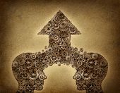 pic of merge  - Business cooperation success teamwork growth concept with two human head shapes merging together to form an upward arrow made of gears and cogs as a financial symbol on a grunge old parchment paper - JPG