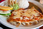 stock photo of ground-beef  - Lunh time in Mexico with enchiladas with cheese and tomato - JPG
