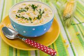 Cream Of Corn Soup In Blue Bowl With Fresh Cob Of Corn On The Side
