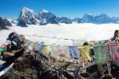 view from Gokyo Ri to Arakam Tse, Cholatse, Tabuche Peak, Thamserku and Kangtega with prayer flags -