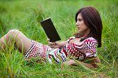 Brunette Girl Reading Book Lying On The Grass