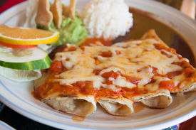 stock photo of enchiladas  - Lunh time in Mexico with enchiladas with cheese and tomato - JPG
