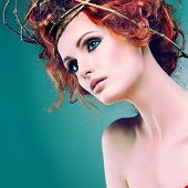 Red hairs. Portrait of beautiful girl  in a chaplet from branches.