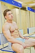 Bodybuilder sits tired leaning back on bench in locker room after finishing training
