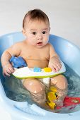 Baby boy bathes in a bathtube with toy dolphin