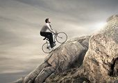 young businessman pedaling a bicycle on the rocks