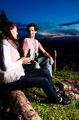 Tyrol - Young couple sitting on alpine meadow of a mountain on Campfire in the Bavarian Alps enjoying the romantic evening sunset of the panorama in leisure time or vacation