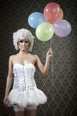 Numb girl in white angel costume with colorful balloons.