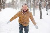 Portrait of happy guy in winterwear having fun in park