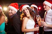 Company of friends in Santa caps holding flutes of champagne while dancing at Christmas party