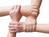 Hands of older people gripping the hands of other older people forming a rectangle in a sign of unio