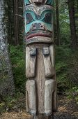 stock photo of totem pole  - Low man on a wooden cedar Tlingit totem pole in a pine forest in Sitka Alaska - JPG