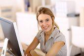 Beautiful blond girl working in office on desktop