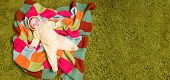 Little Baby Lies On Colorful Blanket