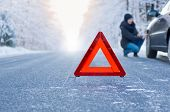image of slippery-roads  - Car breakdown on a country road in winter. Woman crouching beside her car, inspecting the front wheel.
