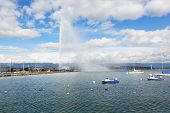A fountain Jet d'Eau rises over the waterfront of Lake Geneva