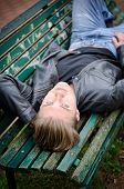 stock photo of down jacket  - Handsome blond young man lying down on green wooden park bench looking at camera - JPG