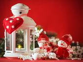 Cute couple of little adorable snowmen is standing near the white fairy lantern with a toy heart on
