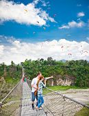 Young couple on the swing suspension bridge taking photos of paragliders in Pokhara, Nepal.