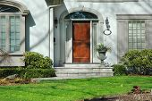stock photo of palladium  - front entrance of home with flower urn and wood door - JPG