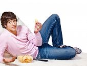 Teenager with crisps  and remote control sits on the carpet