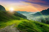 foto of grassland  - meadow on a hillside near the village to the summer cool morning mist - JPG
