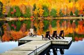 stock photo of dock a lake  - Wooden dock with chairs on calm fall lake - JPG