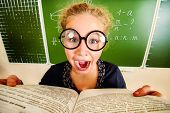Funny schoolgirl in big round glasses opened the book and shouting at camera. Education.