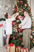 Woman hangs decorations on Christmas tree, man gives her toys