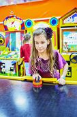 Little girl in violet suit plays air hockey
