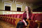 Beautiful woman in red sit in empty auditorium and looks at stage