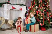 Little boy sits on big cardboard gift box, holding another one in his hands near decorated Christmas tree, little girl tries to take box