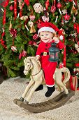 Smiling little girl dressed in santa suit sits on hobby-horse holding lantern with burning tealight