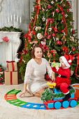 Mother sits on floor under decorated Christmas tree and look at little girl dressed in Santa suit wh