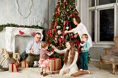 Family of five in room during decorating christmas tree, shot was taken in public rented studio