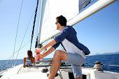 Skipper on sailboat navigating in mediterranean sea