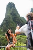 Couple taking photos having fun lifestyle hiking on Hawaii in outdoor activity. Woman and man hiker taking photo pictures with smart phone camera. Iao Valley State Park, Wailuku, Maui, USA.