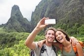 Couple taking selfie photo with smart phone hiking on Hawaii. Woman and man hiker taking photo with