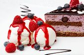 picture of ice-cake  - Three scoops of creamy vanilla ice cream drizzled with berry coulis and served with fresh raspberries and blueberries and a slice of chocolate blueberry cake - JPG