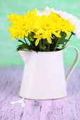 Beautiful chrysanthemum flowers in pitcher on wooden table